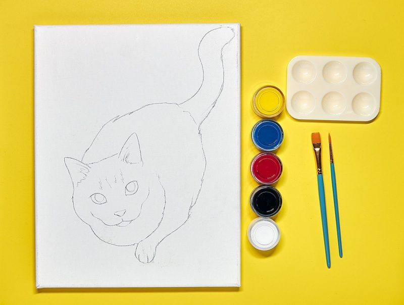painting supplies and a sketch of a cat